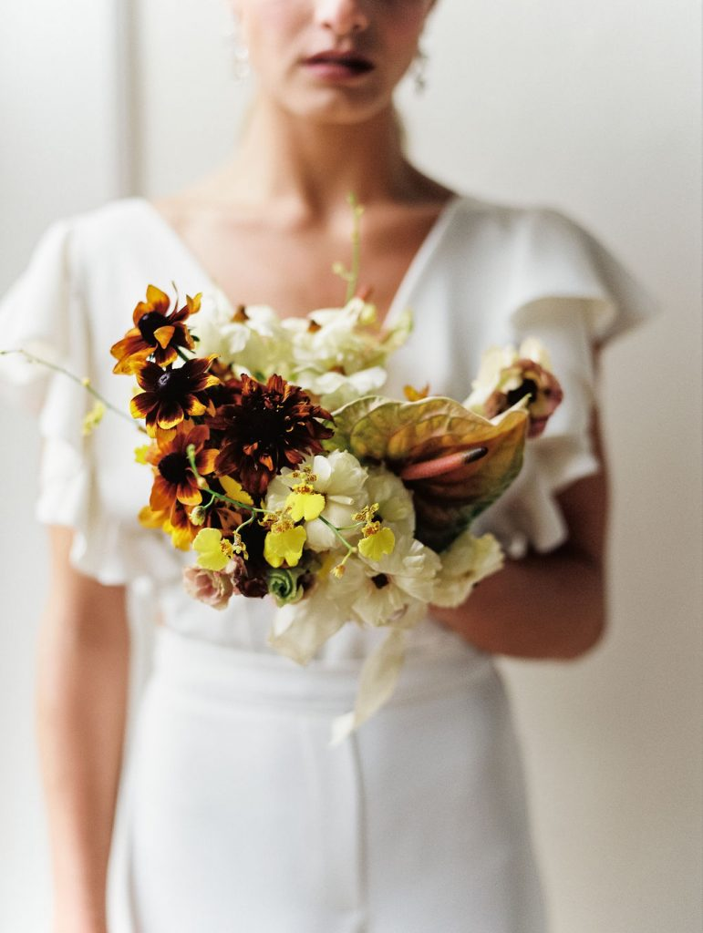 A modern spring bridal bouquet of rudbeckia, orchids, and anthurium in a warm neutrals palette by Nectar and Root, a Vermont wedding florist.