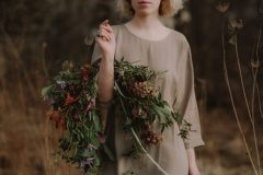 A bride wearing a khaki dress holding a simple fall bridal bouquet of October clematis, vines, wildflowers, jasmine and orchids in a warm neutral palette of rust, orange, and purple by Nectar and Root, Vermont wedding florist in Burlington, Vermont.
