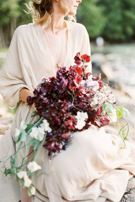 A bride outside wearing a taupe organic wedding dress holding a summer bridal bouquet of July sweet peas in a purple color palette with flowing silk ribbons by Nectar and Root, Vermont wedding florist at Lake Willoughby.
