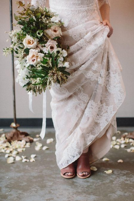 An elopement bride standing with a lush spring classic bridal bouquet of May garden roses, anemones, and sweet peas by Nectar and Root, Vermont wedding florist.