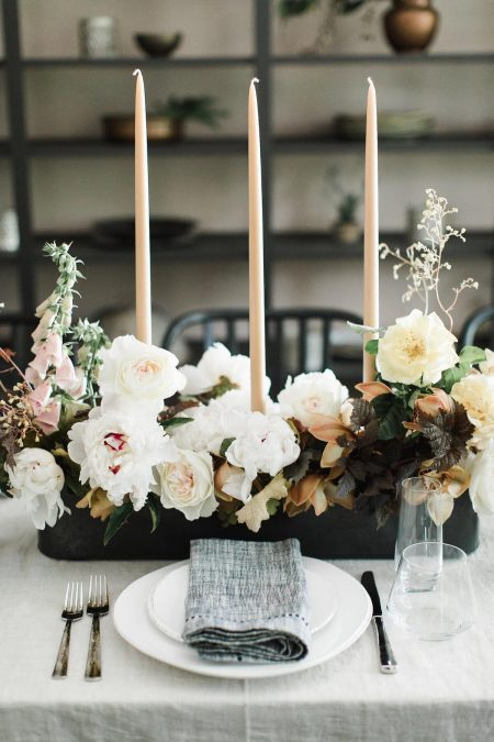 A modern summer reception centerpiece in a dusty neutral color palette atop an indoor reception table with linen napkins featuring garden roses, orchids, and foxglove by Nectar and Root, Vermont wedding florist.